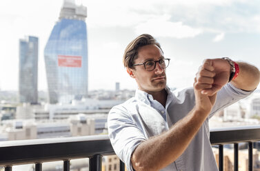 UK, London, man using smartwatch on a roof terrace - MGOF03817