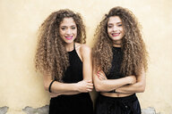 Portrait of laughing twin sisters standing side by side - GIOF04714