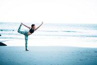 Beautiful woman practicing yoga on the shoreline - INGF02873