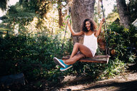 African woman sitting on swing in the garden in summer - INGF02984