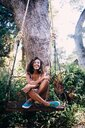 Happy African young woman sitting on swing under tree in garden - INGF03050