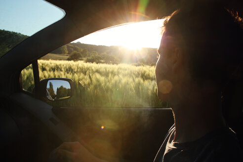 Man looking out of the window in the car as the sun sets - INGF03083