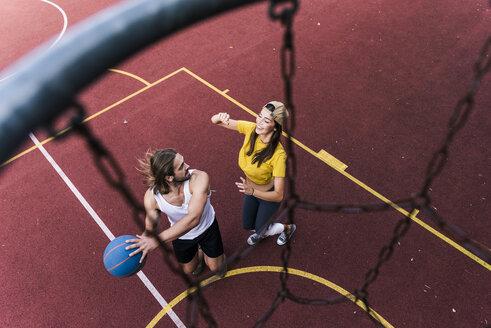 Young man and woman playing basketball on basketball ground - UUF15555