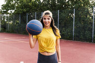 Happy young woman playing basketball - UUF15558