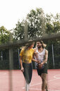 Young couple having fun on the basketball ground - UUF15570