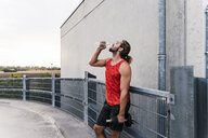 Young man drinking water after training with dumbells - UUF15579