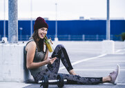 Young woman sitting on ground after dumbbell training, using smartphone - UUF15597