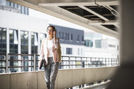 Young businesswoman walking in parking garage, listeing music with her headphones - UUF15609