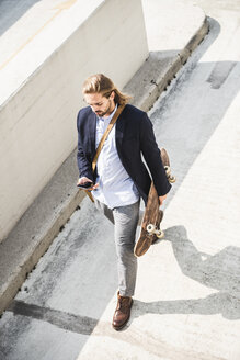 Young businessman carrying skateboard, using smartphone - UUF15621