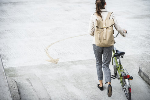 Young businesswoman with backpack, pushing bicycle, rear view - UUF15624