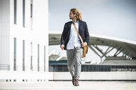 Young businessman walking in the city - UUF15627