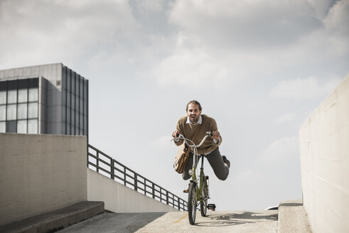 Laughing businessman riding down a ramp on his bicycle - UUF15630