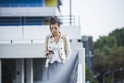 Young businesswoman using smartphone in he city - UUF15636