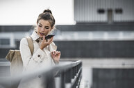Young businesswoman using smartphone in he city - UUF15642