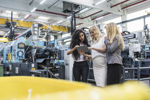 Three women with tablet talking in factory shop floor - DIGF05283