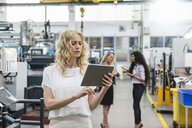 Woman using tablet in factory shop floor with two women in background - DIGF05286