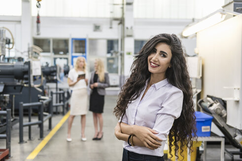 Portrait of smiling woman in factory shop floor with two women in background - DIGF05289