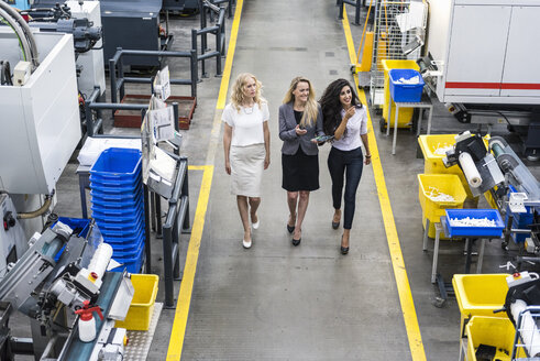 Three smiling women with tablet walking in factory shop floor - DIGF05292