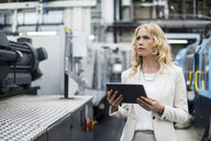 Woman with tablet at machine in factory shop floor looking around - DIGF05295