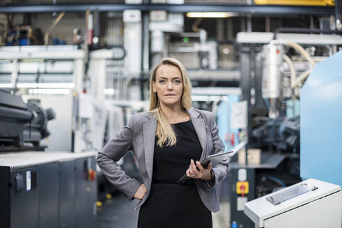 Portrait of confident woman holding tablet in factory shop floor - DIGF05304
