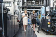 Two women with tablet walking and talking in factory shop floor - DIGF05313