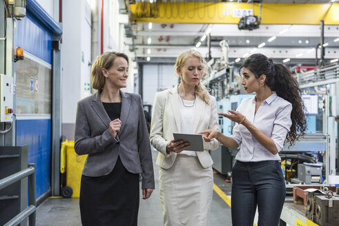 Three women with tablet talking in factory shop floor - DIGF05322