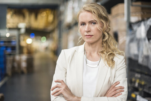Portrait of confident woman in factory storehouse - DIGF05325