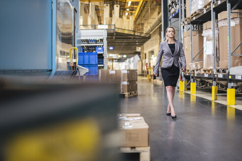 Woman with tablet walking in factory storehouse - DIGF05331