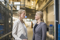 Two women facing each other in factory storehouse - DIGF05337