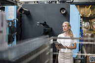 Woman with tablet at machine in factory shop floor looking around - DIGF05343