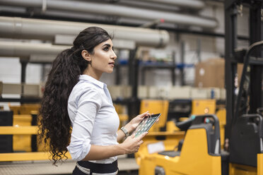 Woman holding tablet in factory shop floor - DIGF05349