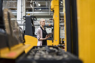 Woman holding tablet in factory shop floor - DIGF05358