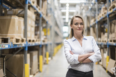 Portrait of confident woman in factory storehouse - DIGF05361
