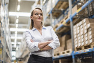Portrait of confident woman in factory storehouse - DIGF05364
