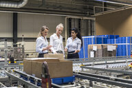Three women discussing at conveyor belt in factory - DIGF05373