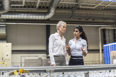 Two women discussing at conveyor belt in factory - DIGF05376
