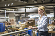 Businesswoman in factory overlooking storehouse - DIGF05379