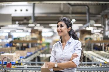 Smiling woman at conveyor belt in factory - DIGF05382