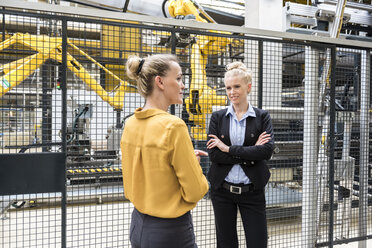 Two women talking in factory shop floor with industrial robot - DIGF05385