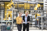 Two women discussing plan in factory shop floor with industrial robot - DIGF05388