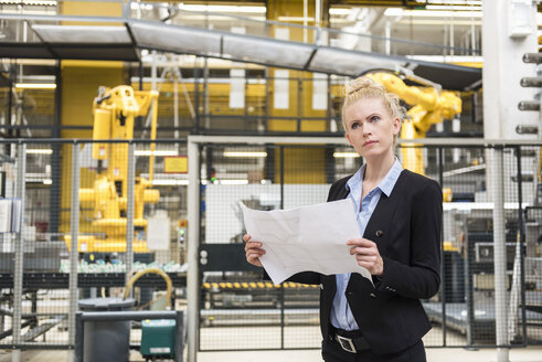 Woman holding plan in factory shop floor with industrial robot - DIGF05391