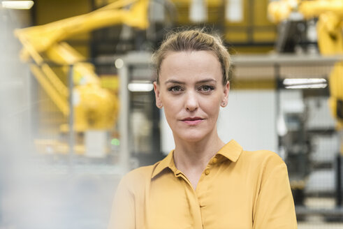 Portrait of confident woman in factory shop floor with industrial robot - DIGF05394
