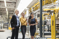 Three women talking in modern factory - DIGF05397