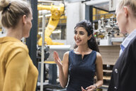Portrait of smiling woman talking to colleagues in modern factory - DIGF05400