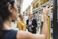 Women with tablet talking in modern factory - DIGF05403