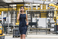 Woman on the phone walking in factory shop floor with industrial robot - DIGF05409