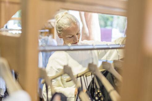 Senior woman shopping for clothes in a boutique - VGF00019