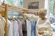 Senior woman shopping for clothes in a boutique - VGF00022