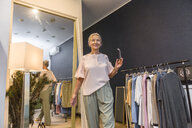 Smiling senior woman walking in a boutique reflected in mirror - VGF00028