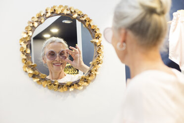 Smiling senior woman trying on sunglasses in a boutique - VGF00031